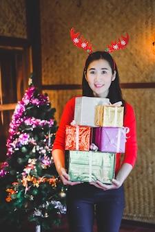 Kobieta niosąca wiele pudełko na święta bożego narodzenia.