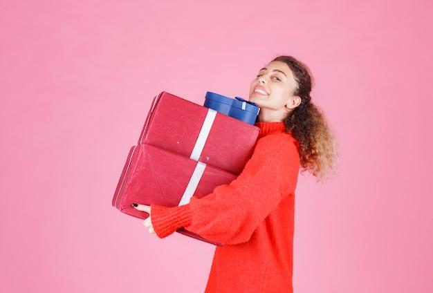 Kobieta niosąca zapas dużych pudełek na prezenty.