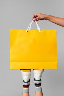 Kobieta niosąca żółtą torbę na zakupy