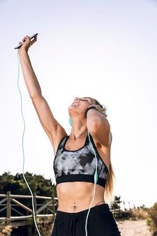 Kobieta niski kąt korzystających z muzyki w słuchawkach