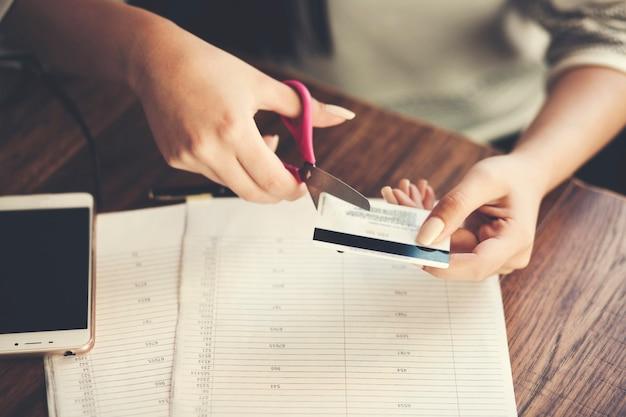 Kobieta niszcząca cięcie karty kredytowej