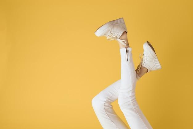 Kobieta nogi białe spodnie i trampki moda