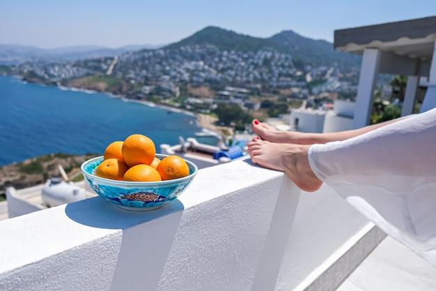 Kobieta nogi i pomarańcze na tarasie bacony domu lub hotelu z widokiem na morze.