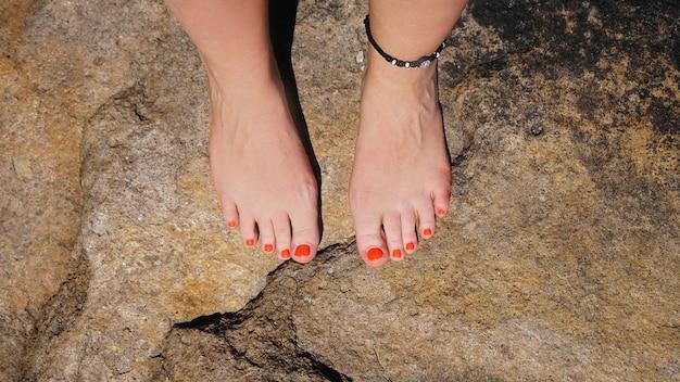Kobieta nogi na kamienistej plaży - kopia przestrzeń. koncepcja wakacji letnich