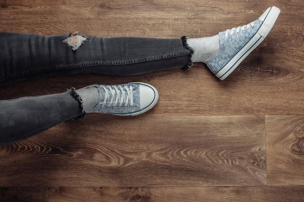 Kobieta nogi nosić w podarte dżinsy i trampki, siedząc na drewnianej podłodze.