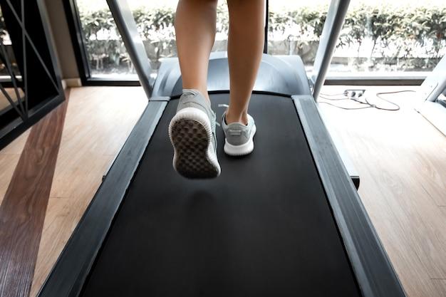Kobieta nogi w butach sportowych biegających na bieżni w siłowni fitness