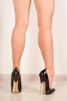 Kobieta nogi w czarnych skórzanych szpilkach z paskiem na kostce
