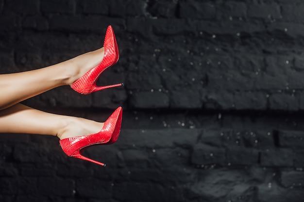 Kobieta nogi w czerwone buty w powietrzu