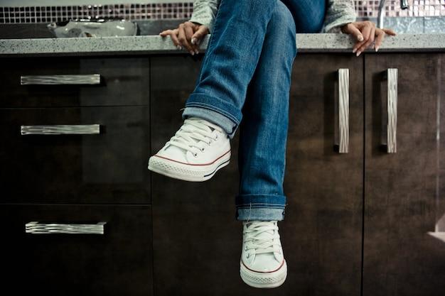 Kobieta nogi w dżinsach i trampkach, siedząc ze skrzyżowanymi nogami w kuchni.