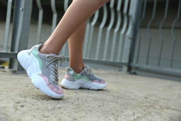 Kobieta nogi w sportowe trampki zewnątrz z bliska