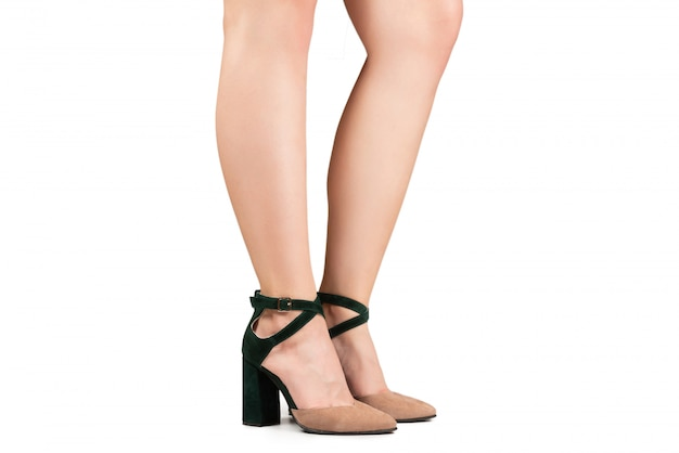 Kobieta nogi w zielone i beżowe sandały na obcasach.