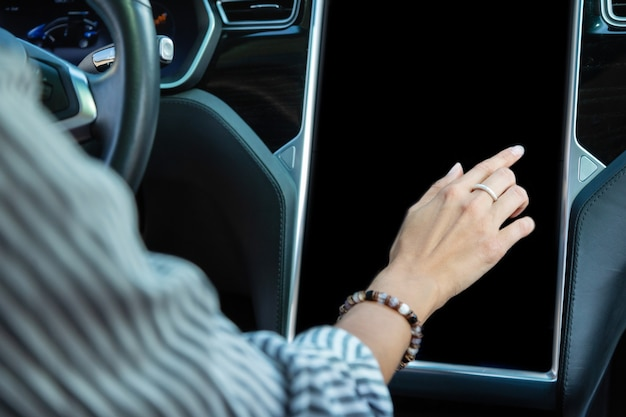 Kobieta nosi bransoletkę. zbliżenie kobiety noszącej bransoletkę za pomocą nawigacji w samochodzie podczas jazdy while