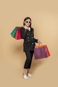 Kobieta nosi ciemne ubrania i okulary, a także wiele toreb, aby iść na zakupy
