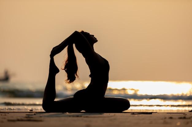 Kobieta nosi czarną odzież sportową uprawiania jogi na plaży