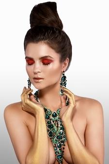 Kobieta nosi duży piękny naszyjnik z dużą ilością klejnotów