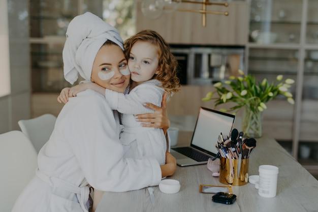 Kobieta nosi hydrożelowe łaty pod oczami ubrana w szlafrok i zawinięty ręcznik z miłością obejmuje swoją małą córeczkę
