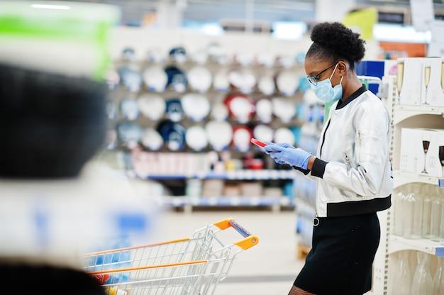 Kobieta nosi jednorazowe maski medyczne i rękawiczki zakupy w supermarkecie podczas wybuchu pandemii koronawirusa.