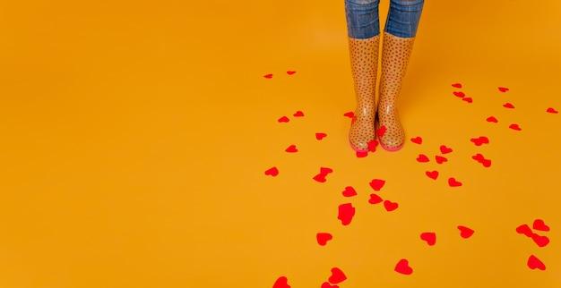 Kobieta nosi kalosze, stojąc na podłodze z wieloma sercami. studio strzał zgrabnej pani w żółtych gumowych butach, pozowanie w walentynki.