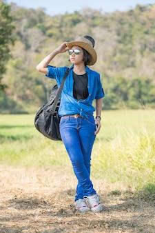 Kobieta nosi kapelusz chodzenia i niesie torbę gitary