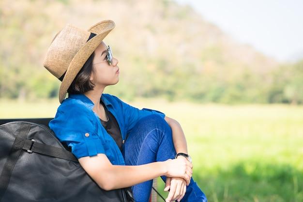 Kobieta nosi kapelusz i nosi torbę na gitarze na pikap