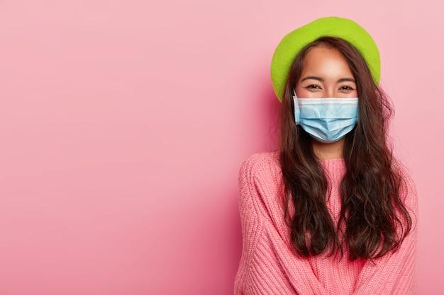 Kobieta nosi maseczkę medyczną chroniącą przed chorobami, nosi zielony beret i duży różowy sweter