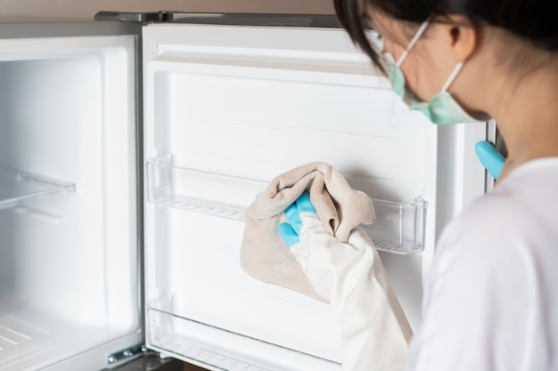 Kobieta nosi maseczkę medyczną, rękawice do czyszczenia nowej lodówki szmatką.