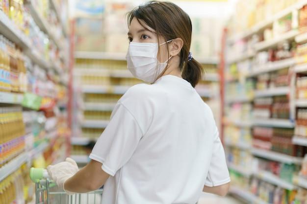 Kobieta nosi maskę chirurgiczną i rękawiczki z wózka na zakupy, robi zakupy podczas pandemii coronavirus.