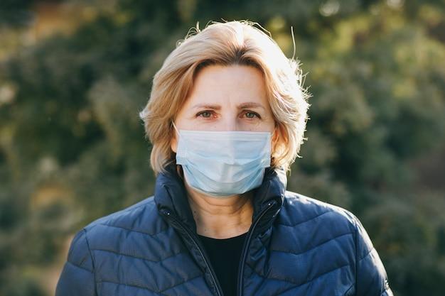 Kobieta nosi maskę medyczną podczas epidemii koronawirusa covid-19. chora kobieta jest ubranym ochronę podczas pandemii.