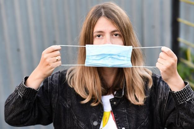 Kobieta nosi maskę medyczną z powodu epidemii wirusa w mieście.