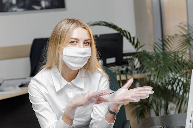 Kobieta nosi maskę ochronną i stawia na rękawiczki.