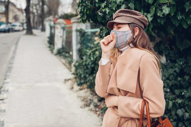 Kobieta nosi maskę wielokrotnego użytku na zewnątrz podczas pandemii koronawirusa covid-19. kobieta kaszle mdłości. trzymać dystans