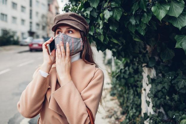 Kobieta nosi maskę wielokrotnego użytku na zewnątrz podczas pandemii koronawirusa covid-19. kobieta rozmawia przez telefon na pustej ulicy. aktualności