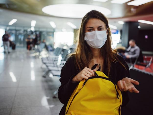 Kobieta nosi maski medyczne żółty plecak opóźnienia lotu czeka. zdjęcie wysokiej jakości