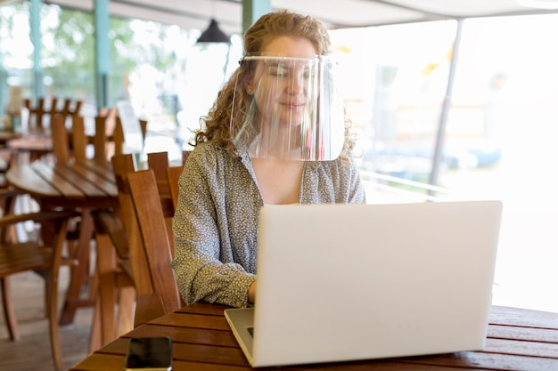 Kobieta nosi ochronę twarzy podczas pracy na laptopie