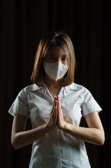 """Kobieta nosi okulary ochronne i maskę. powitanie przez wykonanie """"thai wai"""" lub """"namaste"""" oznacza cześć, aby uniknąć rozprzestrzeniania się koronawirusa."""
