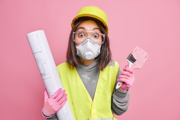Kobieta nosi okulary ochronne kask ochronny z respiratorem trzyma plan i pędzel malarski zamierza odmalować ściany domu pozuje na różowo