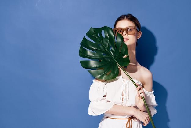 Kobieta nosi okulary przeciwsłoneczne kosmetyki palmowe lato podróżuje niebieska ściana.