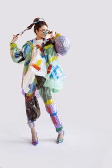 Kobieta nosi plastik na białym tle. modelki w ubraniach i butach ze śmieci. koncepcja mody, stylu, recyklingu, eko i ochrony środowiska. za dużo zanieczyszczeń, jemy i zabieramy.