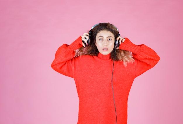 Kobieta nosi słuchawki, aby słuchać muzyki.