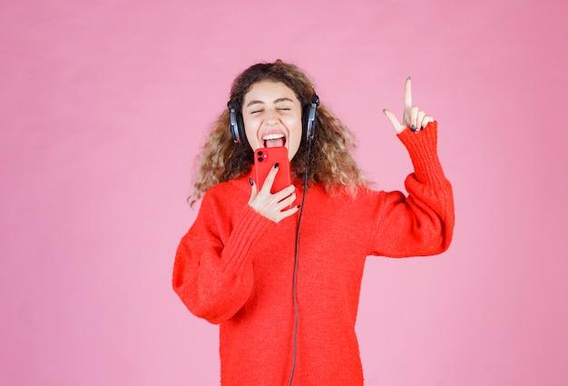 Kobieta nosi słuchawki, słuchając jej listy odtwarzania w smartfonie i taniec.