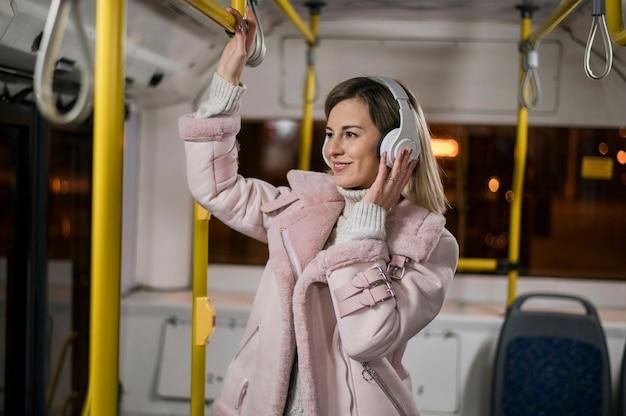 Kobieta nosi słuchawki w autobusie