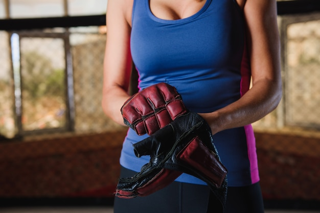 Kobieta nosi sportowe rękawiczki skórzane z bliska
