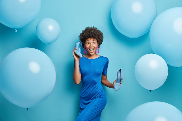 Kobieta nosi sukienkę trzyma buty na wysokim obcasie sukienki na imprezowe pozy na niebiesko