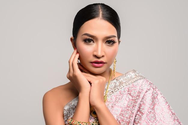 Kobieta nosi tajską sukienkę, a dłonie dotykają twarzy.