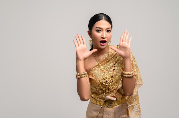 Kobieta nosi tajskie ubrania i otwiera dłonie po obu stronach.