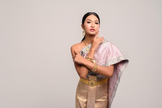 Kobieta nosi tajskie ubrania i ręce dotykając jej twarzy