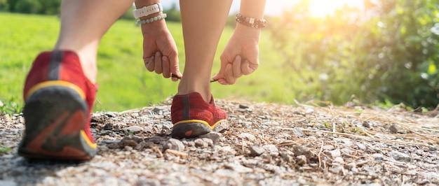 Kobieta nosić buty do biegania na spacery i bieganie na zielonym tle przyrody. koncepcja ćwiczeń zdrowotnych.