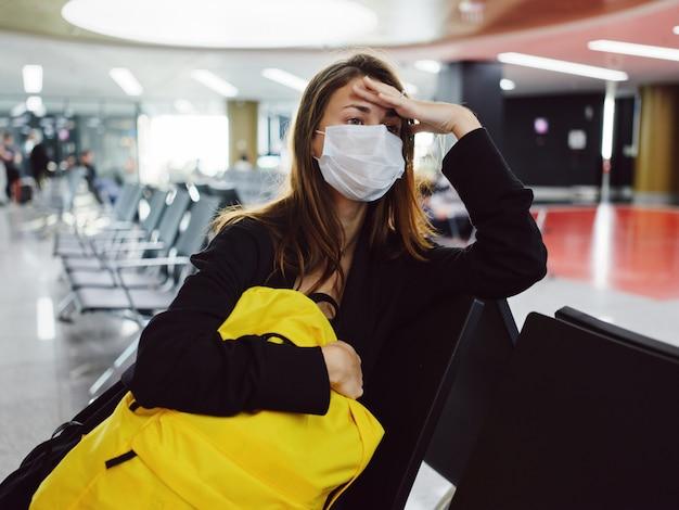 Kobieta nosząca maskę medyczną z zamkniętymi oczami w żółtym plecaku na lotnisku