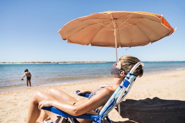 Kobieta nosząca maskę na letnich wakacjach leżąca w słońcu na leżaku tuż obok pomarańczowego parasola, podczas gdy jej syn bawi się na brzegu w środku pandemii koronawirusa