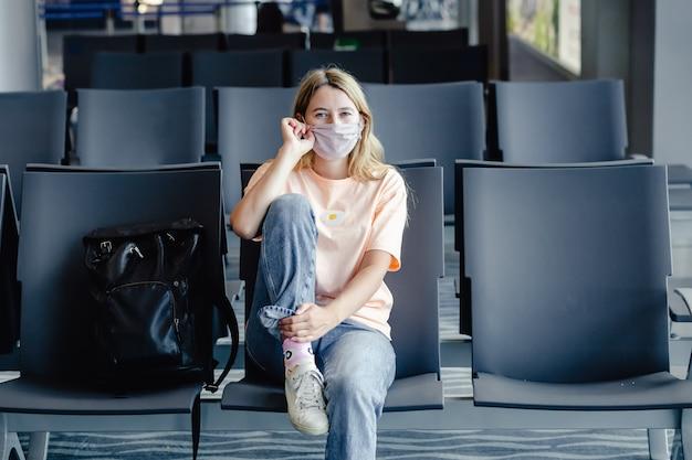 Kobieta nosząca maskę ochronną w celu zapobiegania koronawirusowi lub covid z bagażem na międzynarodowym lotnisku.